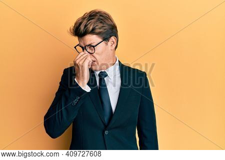Handsome caucasian man wearing business suit and tie smelling something stinky and disgusting, intolerable smell, holding breath with fingers on nose. bad smell
