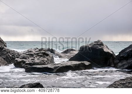 Cold Winter Sea Under A Cloudy Sky Behind Coastal Cliffs