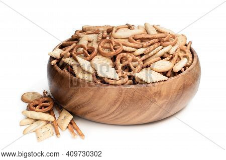 Crunchy  Mix Of Pretzels And Crackers In Wooden Bowl Isolated On White