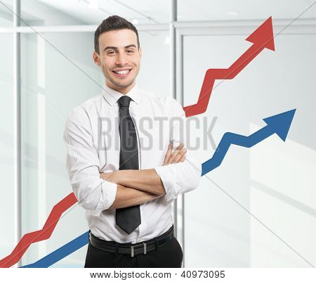 Portrait of an happy businessman standing in front of rising arrows