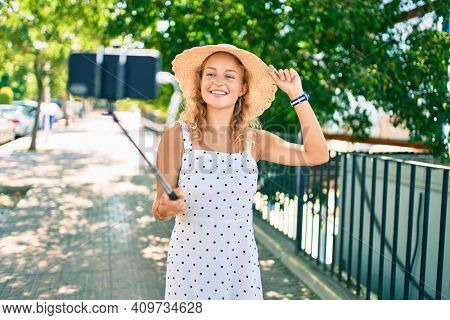 Young beautiful caucasian woman with blond hair smiling happy outdoors taking a selfie picture using selfie stick
