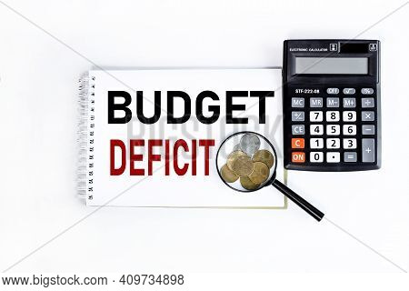 Budget Deficit. Text On White Notepad Paper On White Background Near Calculator And Magnifier