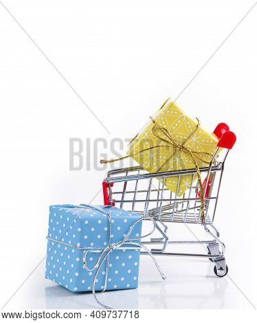 Cart With A Box Of Gifts On A White Background. Holiday And Shopping Concept. Selective Focus.