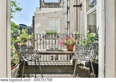 Balcony Full Of Potted Plants With Wooden Table And Two Chairs