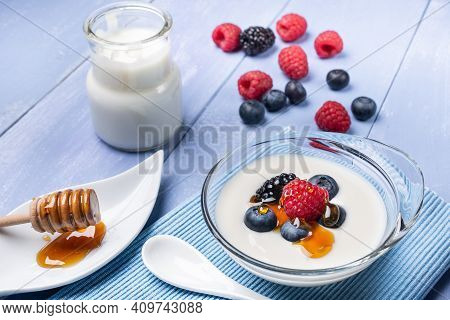 In The Foreground, On The Wooden Table, Some Fresh Berries And A Jar Of Plain And Low-fat Yogurt Wit