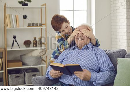 Happy Smiling Little Grandson Covers Grandfathers Eyes And Plays Guess Who Game