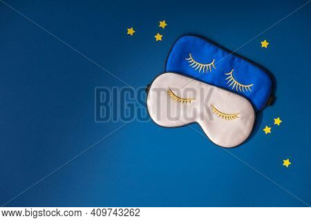 Two sleeping masks and paper stars on blue background, concept of rest, quality of sleep, good night, insomnia, relaxation