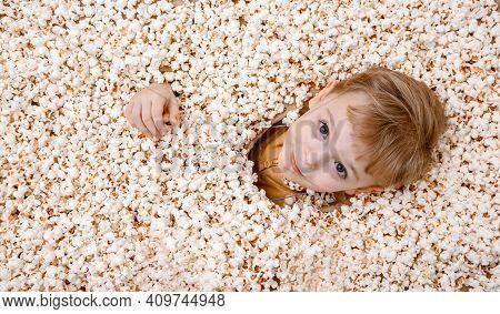 Little Boy Buried In Popcorn. Little Boy Eating Popcorn. Joyful Kid. A Popcorn Background.