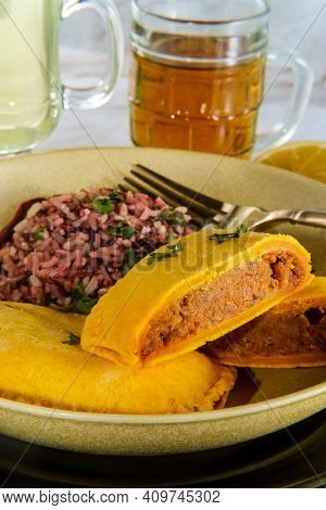 Spicy Jamaican Beef Turnovers With Cilantro Garnish And Purple Rice Served With Beer And Lemonade
