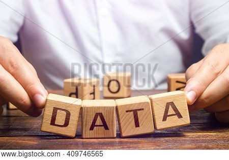 The Man Tries To Pick Up Blocks With The Word Data. Digital Data Integrity And Security Vulnerabilit