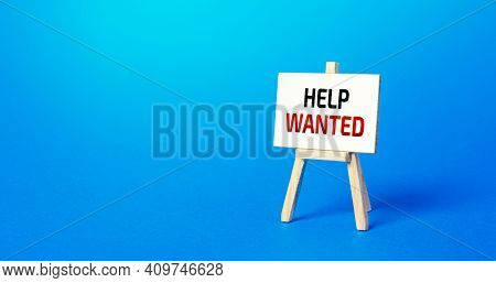 Easel With The Words Help Wanted. Call For Help, Volunteering. Search And Recruitment Of New Employe