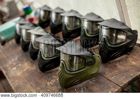 Paintball Masks Lying On A Wooden Table. Paintball Hats Lie On A Wooden Table.