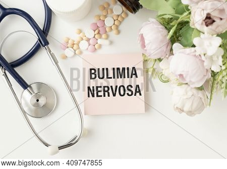 The Word Bulimia Nervosa Written On A White Notepad On A Blue Background Near A Stethoscope, Syringe