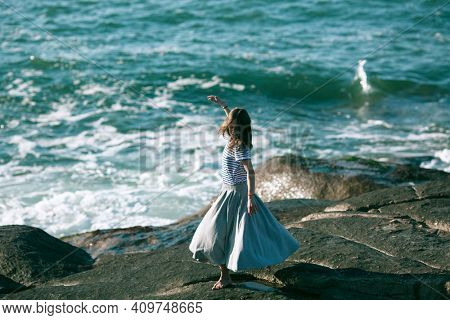 Dancer woman is engaged in choreography on the rocky coast of Atlantic ocean in Portugal.
