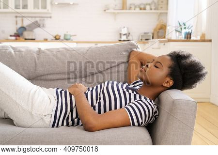 African American Young Woman Wear Stripped T-shirt Sleeping On Couch With Arm Under Head At Home, Cl