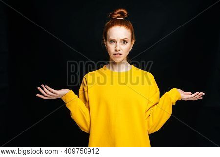 Confused Young Woman Wearing Yellow Sweater Shrugging Shoulders On Isolated Black Background, Lookin
