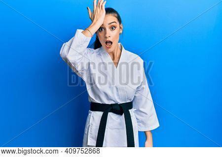 Beautiful brunette young woman wearing karate fighter uniform with black belt surprised with hand on head for mistake, remember error. forgot, bad memory concept.