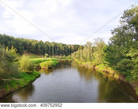 A Wide River With Tall Willows On Its Banks, Blue Sky With Light Clouds. Summer Landscape