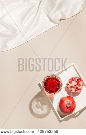 Pomegranates With A Glass Of Juice On A White Wooden Tray With Silk Cloth On Pastel Beige Backgound.