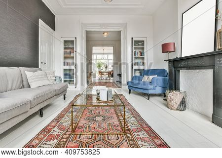 Living Room With Red Carpet, Mild Sofa, Glass Table, And Other Furniture