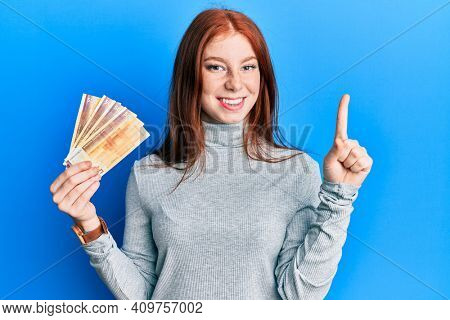 Young red head girl holding 500 norwegian krone banknotes smiling with an idea or question pointing finger with happy face, number one