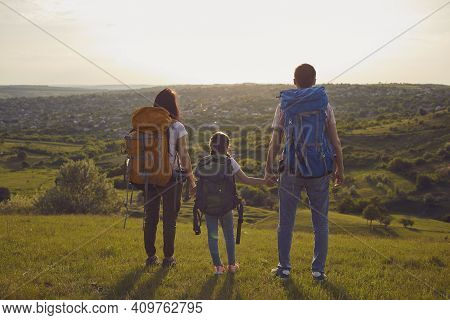 Family With Backpacks. Hiker Mother Father And Daughter With Backpacks In Nature. Back View.