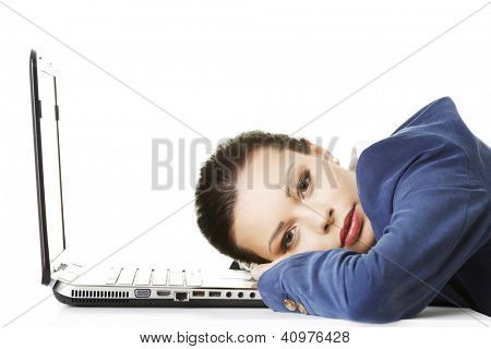 Beautiful bored and tired businesswoman lying down on desk next her laptop poster