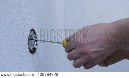 Tightening The Bolt Tightly Into The Frame Of The Double Socket Using A Screwdriver, Force And Press