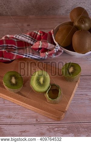 Half Kiwifruit With Skin On Wooden Board, Bowl With Whole Kiwifruit, Wooden Plank Floor, Red And Whi