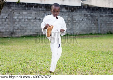 Child Practicing Karate Alone In The Park