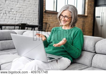 Cheerful Senior Woman Has A Video Conference On The Laptop Sitting On The Couch At Home, An Elderly