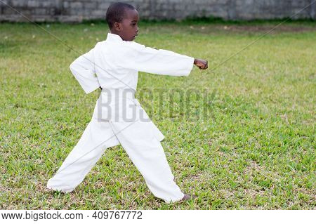 Profile Of A Young Boy In A Kimono Practicing Karate Alone In The Park