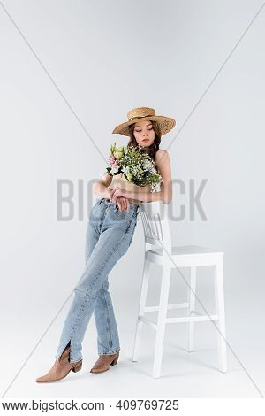 Young Model In Jeans, Shoes And Flowers In Blouse Standing Near Chair On Grey Background.