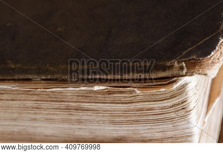 Close-up Of The Corner Of An Old Book With Frayed Edges Of The Cover.