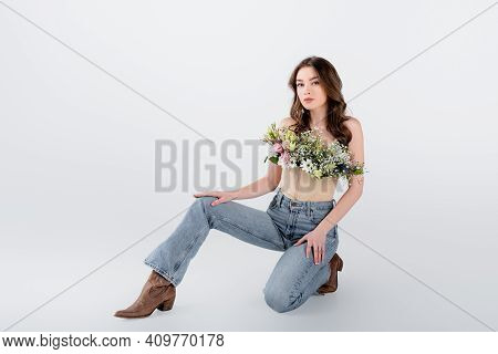 Brunette Woman In Brown Shoes, Jeans And Flowers In Blouse On Grey Background.