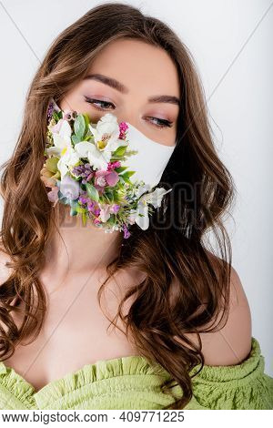 Woman In Medical Mask With Flowers And Green Blouse Looking Away Isolated On Grey.