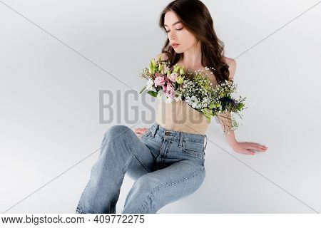 Woman In Jeans And Blouse With Flowers Sitting Isolated On Grey.