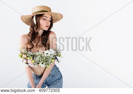 Model With Flowers In Blouse Posing In Sun Hat Isolated On Grey.