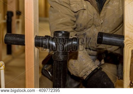 Plumber Jointing Glue Pvc Sewage Drain Pipes On A House Under Construction