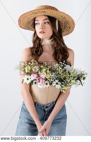 Model In Sun Hat With Flowers In Blouse Isolated On Grey.