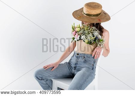 Woman With Flowers In Blouse And Sun Hat Sitting On White Chair Isolated On Grey.