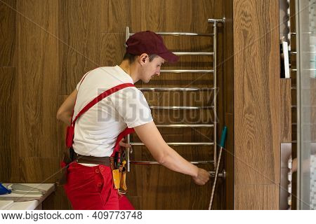 Grinding Of A Stainless Heated Towel Rail. The Master Repairs The Heated Towel Rail