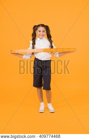 Measuring Length. Little Girl Holding Metric Ruler On Yellow Background. Small Girl Preparing For Ma