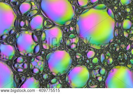 Textural Foam Surface Of Soap Or Shampoo With Bubbles Of Pink, Yellow And Blue Colors. Abstract Past