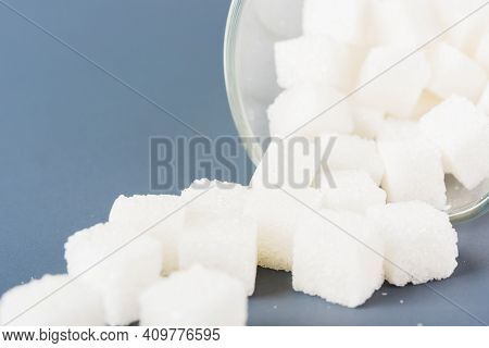 White Sugar Cube Sweet Food Ingredient Spilled Out Of The Glass, Studio Shot Isolated On A Gray Back