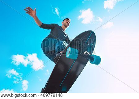 Skateboarder In Action, Making Trick. Man Riding On A Skateboard Outdoors On Sunny Summer Day. Summe