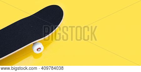 Black Skateboard On Yellow Background. Copy Space