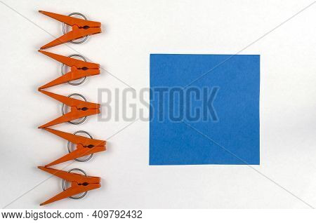 Brown Plastic Clothespins And Blue Paper Square On A White Background. A Line Of Clothespins And A S