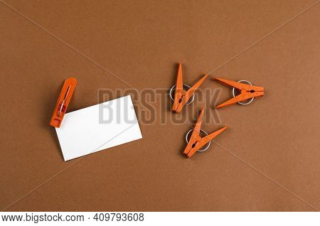Brown Plastic Clothespins And White Blank Business Card On Brown Background. New Clothespins. Top Vi