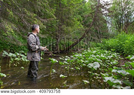 Angler Spinningist With A Spin Fishing Rod In His Hands Stands In The Middle Of A Narrow Forest Rive